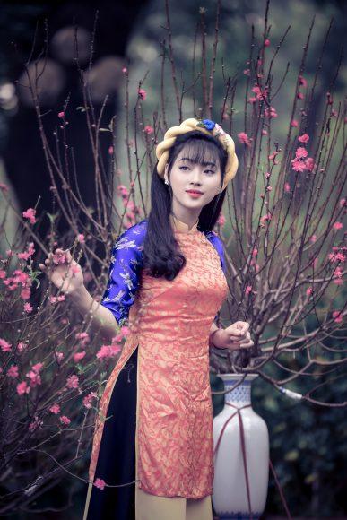 ảnh cô gái khoe sắc bên hoa đào ngày tết
