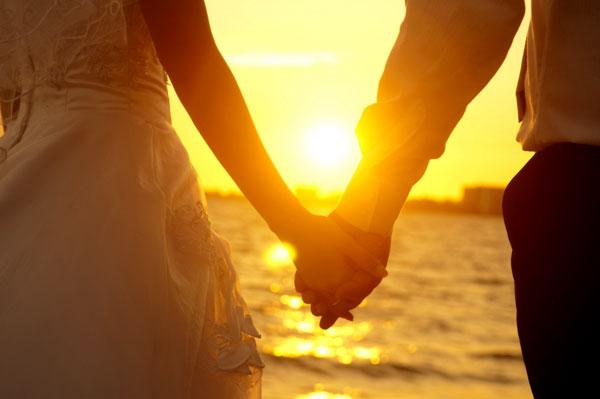 ảnh hai người nắm tay nhau trong chiều hoàng hôn bên bờ biển
