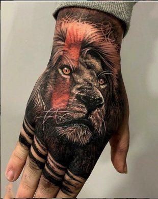 hình xăm sư tử với đôi mắt sáng rực trên mu bàn tay