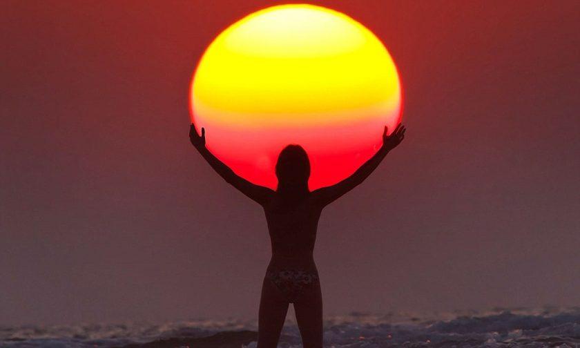 hình ảnh người dang tay như ôm lấy mặt trời hoàng hôn