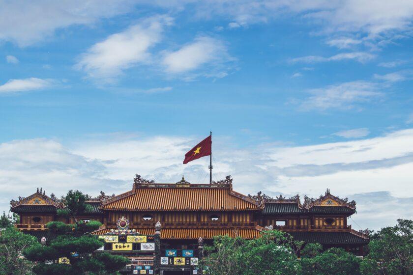 ảnh lá cờ Việt Nam - lá cờ tung bay trện nóc một tòa điện torng kinh thành Huế