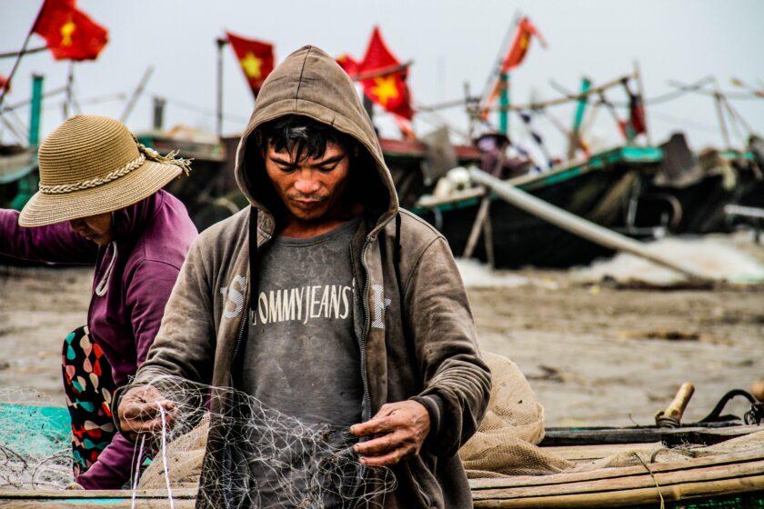 ảnh lá cờ Việt Nam - người ngư dân cần mẫn cùng hàng chục lá cờ trên những chiếc thuey62n neo đậu tại bến