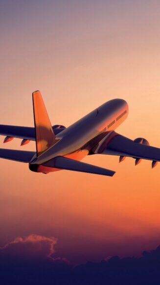Hình ảnh máy bay đang bay trên bầu trời rực đỏ